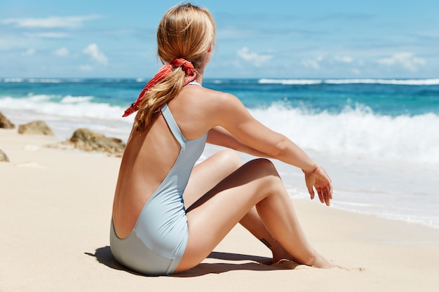 Blondynki kobieta z kostiumem kąpielowym na plaży