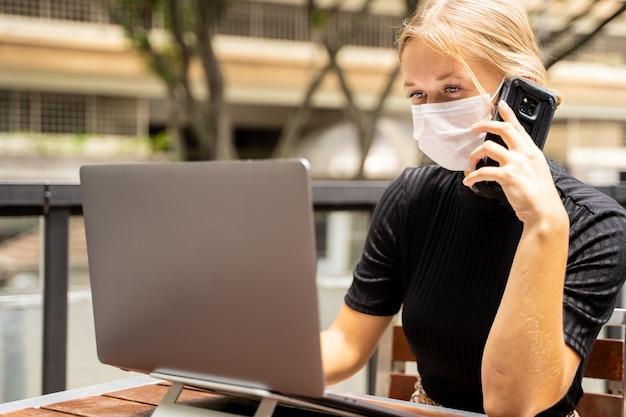 Blondynki kobieta z maską ochronną na jej twarzy pracuje zdalnie z jej laptopem podczas gdy opowiadający jej telefon komórkowy
