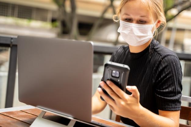 Blondynki kobieta z maską ochronną na jej twarzy pracuje zdalnie z jej laptopem podczas gdy używać jej telefon komórkowego