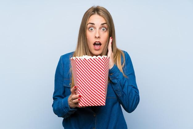 Blondynki kobieta z popcorns nad błękit ścianą robi niespodzianka gestowi