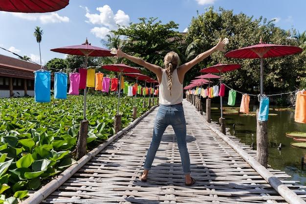 Blondynki kobieta z rękami w powietrzu z gestem wolności po środku drewnianego mostu z kolorowymi parasolami