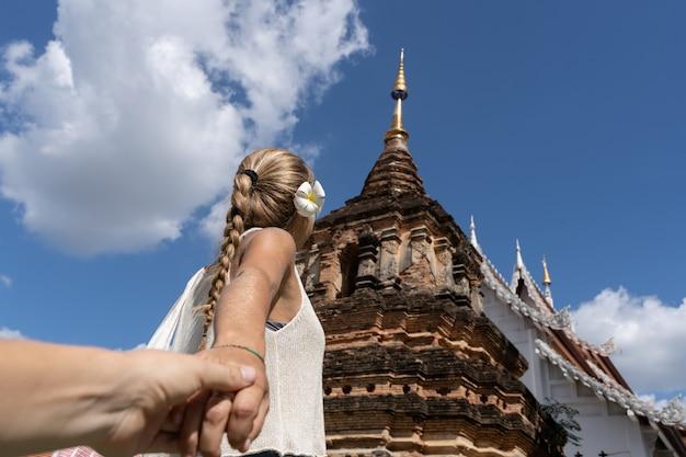 Blondynki kobieta z warkoczem i kwiatem w jej uchu trzyma ręki przed buddyjską świątynią