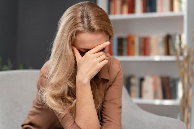 Blondynki kobieta zakrywająca twarz ręką