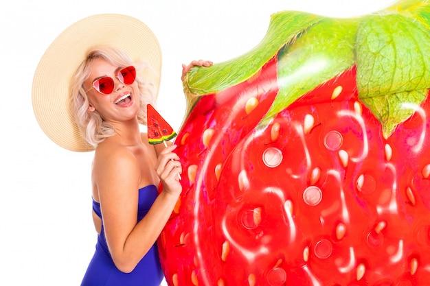Blondynki kobiety caucasian stojaki w swimsuit z gumy plażowym materac i uśmiechami odizolowywającymi na białym tle