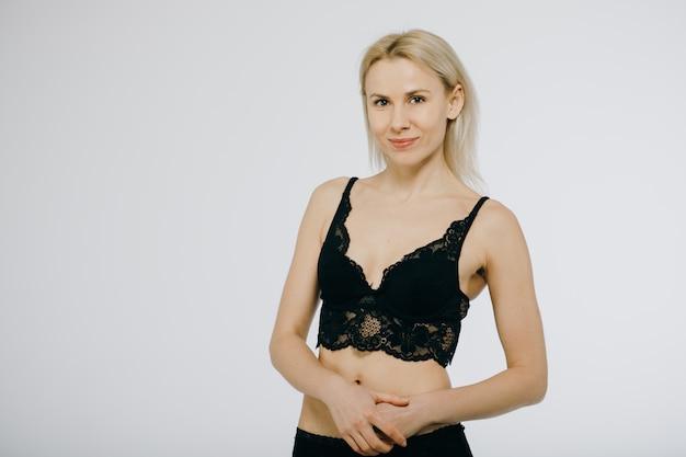 Blondynki kobiety szczęśliwy uśmiechu pozuje odzież w czarnej bieliźnie, staniku i majtasach. studio izolowanych ponad białym