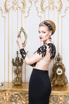 Blondynki królewska kobieta stoi blisko retro stołu w wspaniałej luksus sukni z kieliszkiem wina w jej ręce. wnętrz. kopiuj przestrzeń