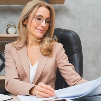 Blondynki młodej kobiety obsiadanie na krześle sprawdza biznesowych dokumenty przy miejscem pracy