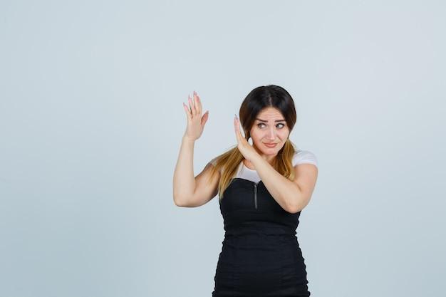 Blondynki młoda dama gestykuluje w sukni na białym tle