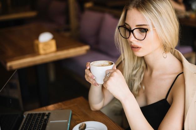 Blondynki młoda kobieta jest ubranym eyeglasses trzyma filiżankę w caf���
