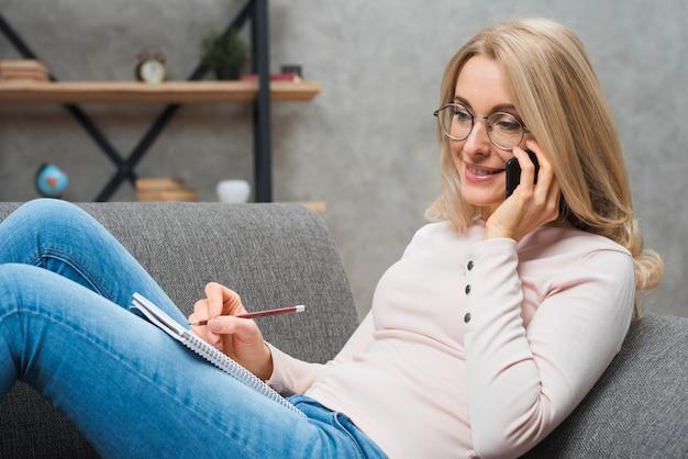 Blondynki młoda kobieta opowiada na telefonu komórkowego writing na ślimakowatym notepad z ołówkiem