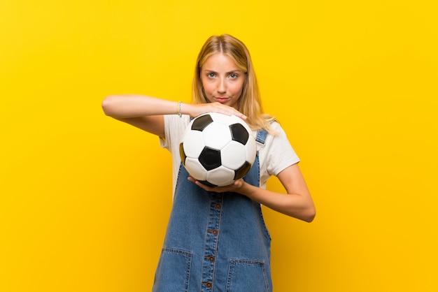 Blondynki młoda kobieta trzyma odosobnioną kolor żółty ścianę trzyma piłki nożnej piłkę