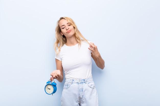 Blondynki młoda kobieta trzyma zegar patrzeje arogancki wskazuje jaźń