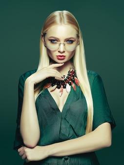 Blondynki młoda kobieta w eleganckiej zieleni sukni.