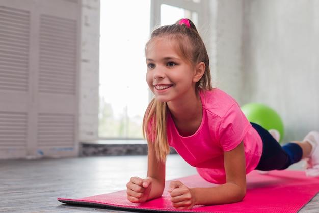Blondynki młoda uśmiechnięta dziewczyna robi sprawności fizycznej ćwiczeniu