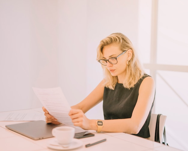 Blondynki młodej kobiety czytania dokumenty przy miejscem pracy w biurze
