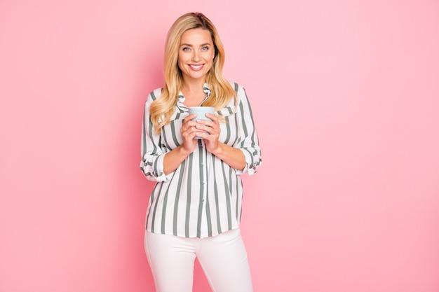 Blondynki modna dama pozuje na różowej ścianie