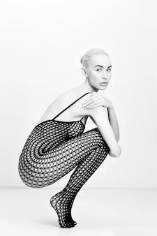 Blondynki naga kobieta w seksownej bieliźnie siedzi na podłodze. nagie idealne nagie dziewczyny w czarnej erotycznej bieliźnie w siatce. naga dziewczyna pozuje na białym tle
