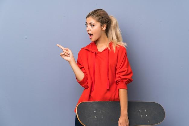 Blondynki nastolatka łyżwiarki dziewczyna nad szarości ścianą zaskakującą i wskazuje stronę