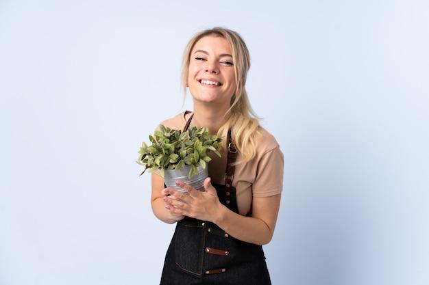 Blondynki ogrodniczki kobieta trzyma rośliny nad odosobnionym oklaskiwać