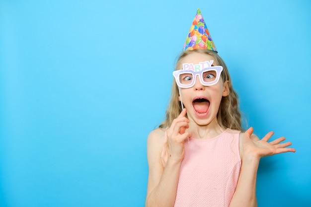 Blondynki rozochocona dziewczyna w śmiesznych szkłach z słowem bawi się. wszystkiego najlepszego z okazji urodzin