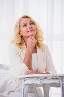 Blondynki starsza kobieta patrzeje daleko od