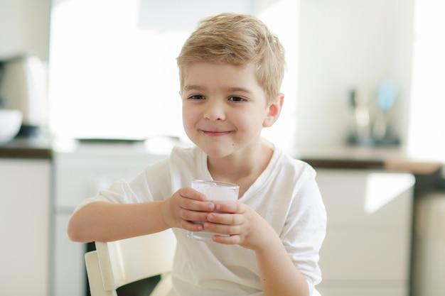 Blondynki szczęśliwa chłopiec pije jogurt dla śniadania w ranku