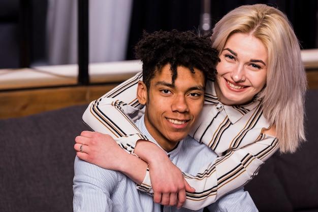 Blondynki uśmiechnięta młoda kobieta obejmuje jej afrykańskiego chłopaka