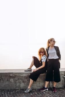 Blondynki w okularach przeciwsłonecznych idą promenadą nad jeziorem garda we włoszech.