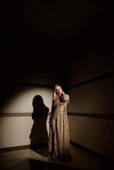 Blondynów dziewczyny model plus pozować w promieniu światło w studiu