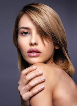 Blone kobieta z krótkimi włosami i grzywką. seksowna blondynka. atrakcyjny blond model z niebieskimi oczami. modelka z smokey makijaż. zbliżenie portret ładnej kobiety. kreatywna krótka fryzura.
