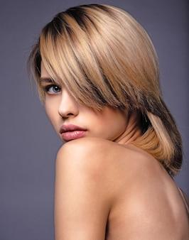 Blone kobieta z krótkimi włosami i grzywką.