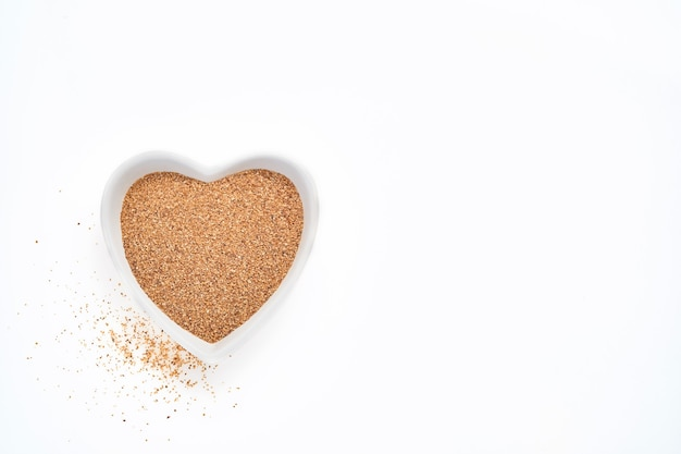 Błonnik topinamburu w misce w kształcie serca na białym stole na białym stole, widok z góry