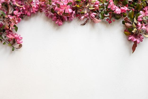 Blossom różowe kwiaty jabłoni jako wiosna rama na białym stole.