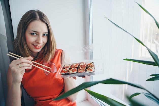 Blueeyed kaukaska dziewczyna w tradycyjnej chińskiej sukni je laski sushi.