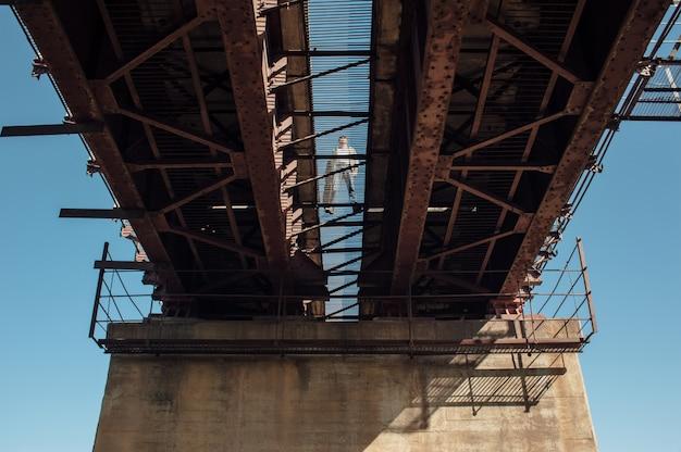 Bluesman w skrzynce na gitarę chodzi po moście kolejowym. sylwetka bluesa muzyk na ośniedziałym kolejowym moscie. fajny facet z gitarą. brodaty mężczyzna podróżuje światło.
