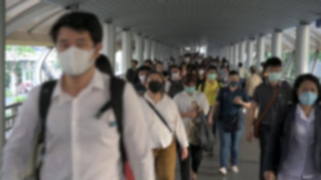 Blured rozmyte. tłum ma na sobie maski ochronne zapobiegające wirusowi koronawiru, wirusowi covid 19 podczas wybuchu wirusa i kryzysowi zanieczyszczenia powietrza pm2,5 w bangkoku w tajlandii.
