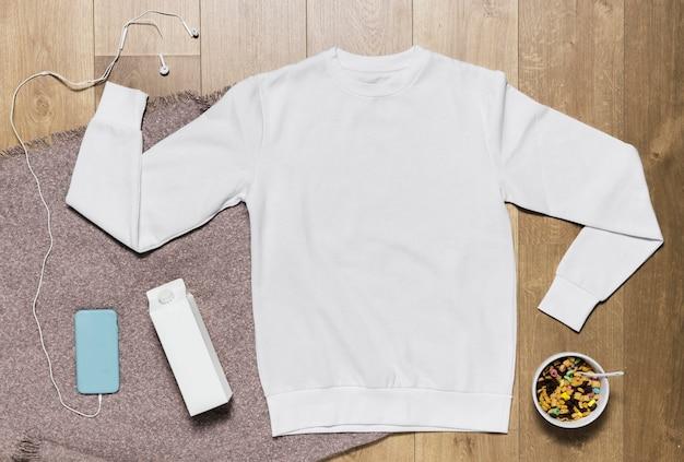 Bluza z kapturem i miska ze zbożami i mlekiem obok