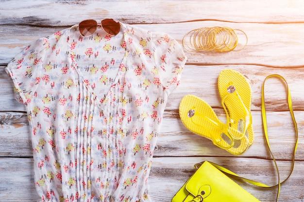 Bluzka z dekoltem w serek i klapki. żółte obuwie i bransoletki damskie. ubrania na białej drewnianej podłodze. ubierz się na lato.