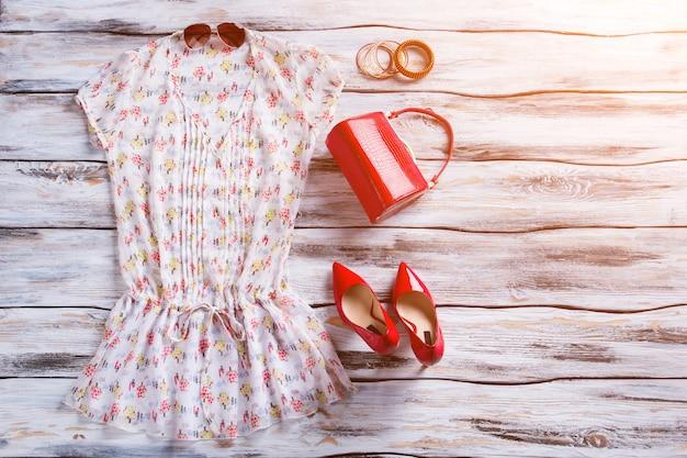 Bluzka z dekoltem w szpic i butami na obcasie. czerwone obuwie i torebka kobiety. atrakcyjne kolory i stylowy wzór. odzież z nowej kolekcji.