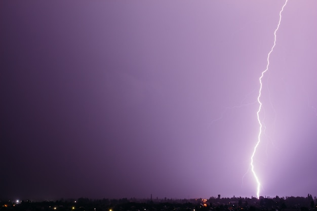 Błyskawica na ciemnym fioletowym niebie uderza w ziemię nad miastem