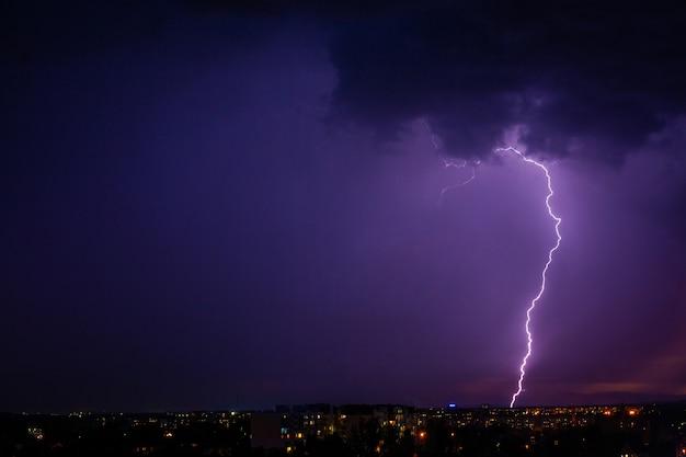 Błyskawica uderza burzę nad fioletowym światłem miasta.