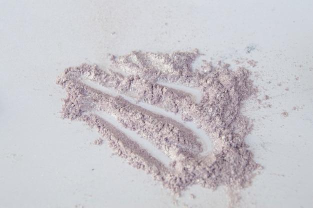 Błyskotliwy różowy i srebrzysty cień do powiek rozrzucone na białym tle