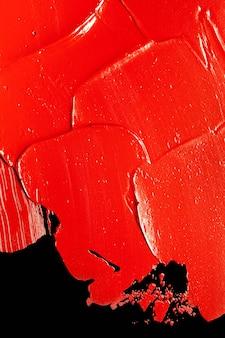 Błyszcząca czerwona szminka rozmazana tekstura na czarnym tle