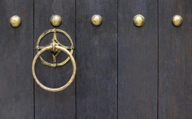 Błyszcząca kołatka z litego mosiądzu metalowa okrągła na stare ciemne drewniane drzwi.