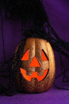 Błyszcząca pomarańczowa dynia halloween z pomarańczowymi świecącymi oczami na błyszczącym fioletowym tle z czarnymi nitkami.
