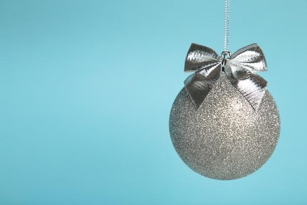 Błyszcząca srebrna bombka z kokardą na niebieskim tle. widok z góry
