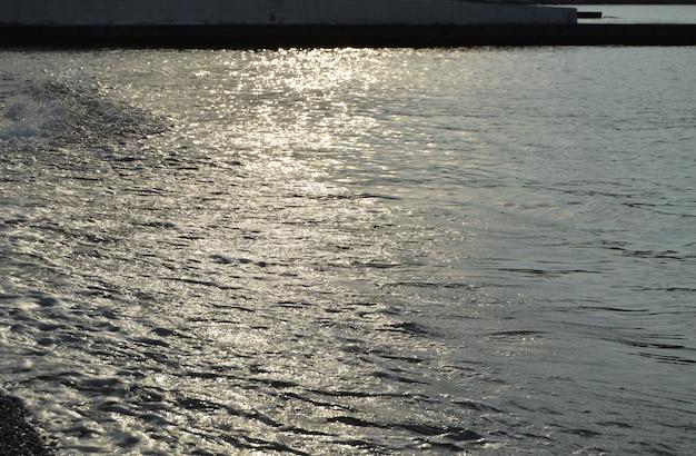 Błyszcząca srebrna woda na plaży żwirowej morza, wschód słońca wczesnym rankiem