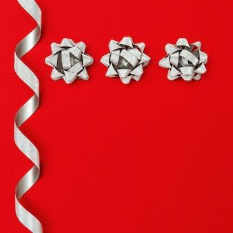 Błyszcząca srebrna wstążka i łuk na czerwonym tle papieru