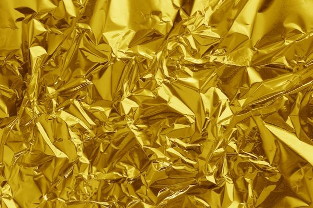 Błyszcząca tekstura liści złotej folii, streszczenie żółty papier pakowy i dzieła sztuki projektowania.