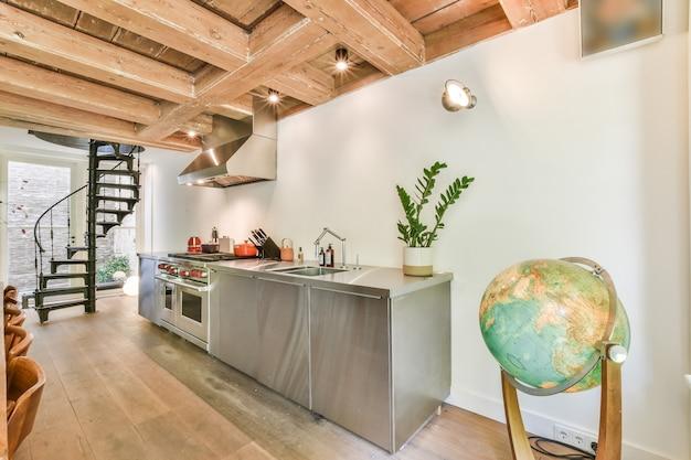 Błyszczące chromowane szafki i urządzenia nowoczesnej kuchni w wiejskim domu z drewnianymi belkami stropowymi i spiralnymi schodami
